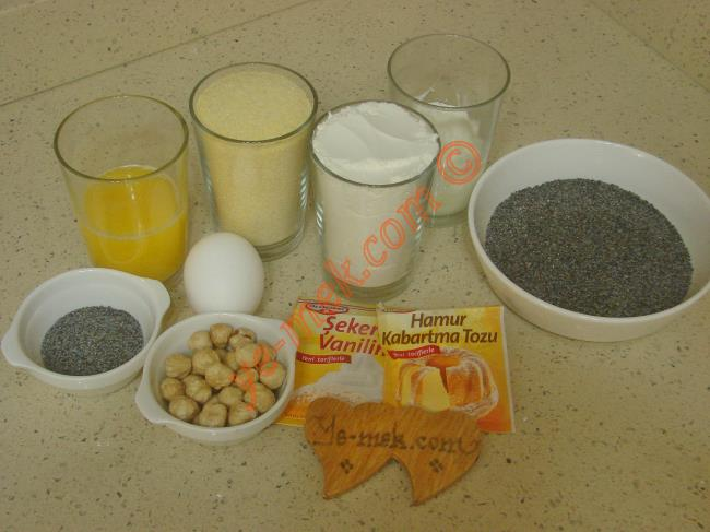 Haşhaşlı Hira Tatlısı İçin Gerekli Malzemeler :  <ul>          <li>1 adet yumurta</li>         <li>1 su bardağı irmik</li> <li>1/2 su bardağı yoğurt</li> <li>1/2 su bardağı eritilmiş tereyağı</li> <li>1 tatlı kaşığı kabartma tozu</li>         <li>1 paket vanilya</li>         <li>1 su bardağı un</li>         <li>1 yemek kaşığı mavi haşhaş</li> <li><strong>Bulamak İçin:</strong></li>         <li>3 yemek kaşığı mavi haşhaş</li>         <li><strong>Üzeri İçin:</strong></li>         <li>Fındık ya da ceviz</li>         <li><strong>Şerbeti İçin:</strong></li>         <li>2 su bardağı sıcak su</li> <li>2 su bardağı toz şeker</li>         <li>2 damla limon suyu</li> </ul>