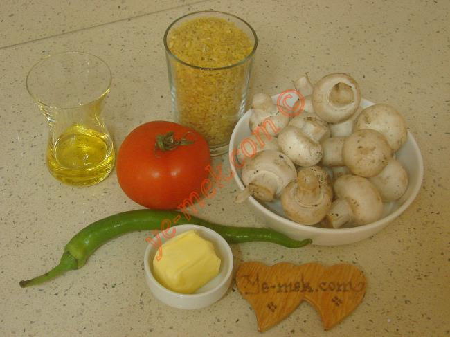 Mantarlı Bulgur Pilavı İçin Gerekli Malzemeler :  <ul>         <li>1 su bardağı pilavlık bulgur</li> <li>200 gr kültür mantarı</li>         <li>1 adet orta boy domates</li>         <li>1 adet sivri biber</li> <li>1 diş sarımsak</li> <li>1/2 yemek kaşığı tereyağı</li>         <li>2 yemek kaşığı zeytinyağı</li> <li>1,5 su bardağı sıcak su</li> <li>Tuz</li> </ul>