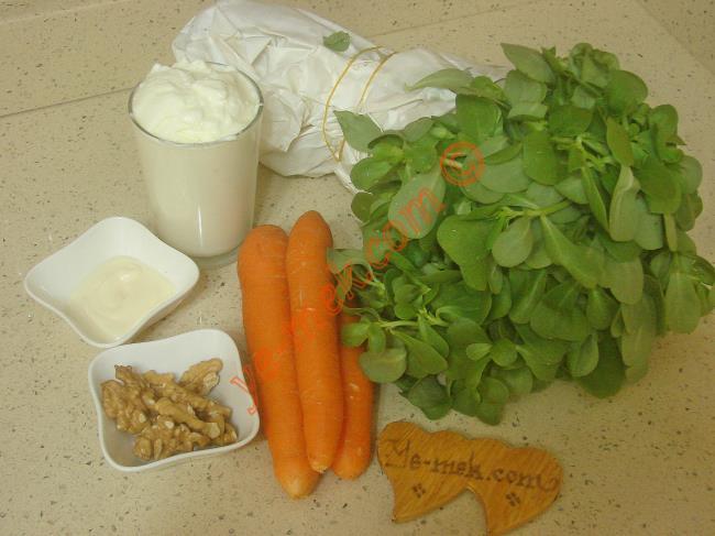 Havuçlu Semizotu Salatası İçin Gerekli Malzemeler :  <ul> <li>1/2 demet semizotu</li> <li>3 adet orta boy havuç</li>         <li>1 yemek kaşığı mayonez</li>         <li>1,5 su bardağı yoğurt</li>         <li>1 diş rendelenmiş sarımsak</li>         <li>3 yemek kaşığı orta dövülmüş ceviz</li> <li>Tuz</li> </ul>