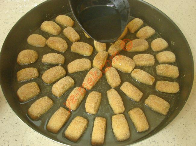 Pişen tatlıyı fırından çıkartıp, üzerine soğuk şerbeti dökün. Üzerini örtüp, şerbetini çekip soğuyana kadar bekletin.