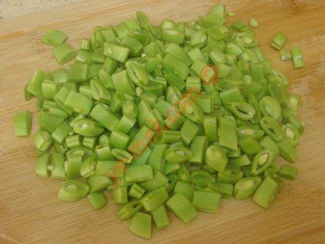 Taze fasulyeli bulgur pilavı yapmak için ilk olarak 200 gr taze fasulyeyi temizleyip, küçük küçük doğrayın. 2 adet yeşil biber, 1 adet kırmızı kapya biber ve 1 adet soğanı ince ince doğrayın.