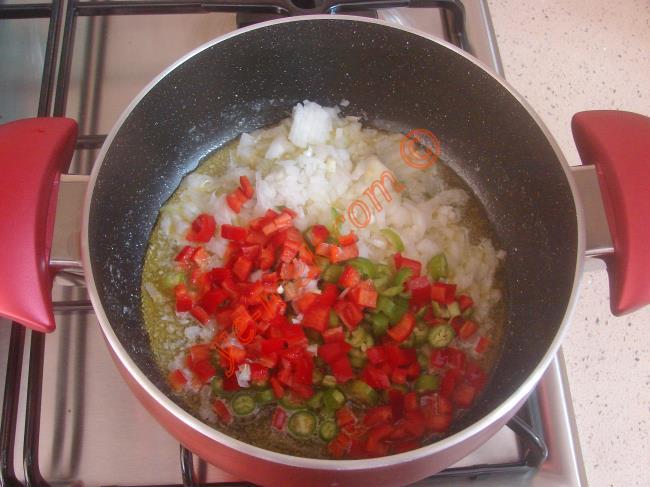 1 diş sarımsak ve 1 adet orta boy domatesi de minik küpler halinde kesin.    Daha sonra derin bir tencere 1 yemek kaşığı tereyağı ve 3 yemek kaşığı zeytinyağı koyup, ısıtın.