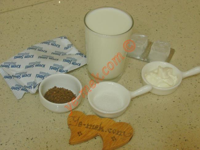 Frappuccino İçin Gerekli Malzemeler :  <ul> <li>1 su bardağı soğuk süt</li> <li>1,5 tatlı kaşığı nescafe</li>         <li>3 parça buz küpü</li> <li>1 tatlı kaşığı toz şeker</li>         <li>1 tatlı kaşığı krema</li> <li><strong>Üzeri İçin:</strong></li>         <li>1/2 paket krem şanti tozu</li>         <li>1/2 su bardağı soğuk süt</li>         <li>Rendelenmiş çikolata ya da çikolata sosu</li> </ul>