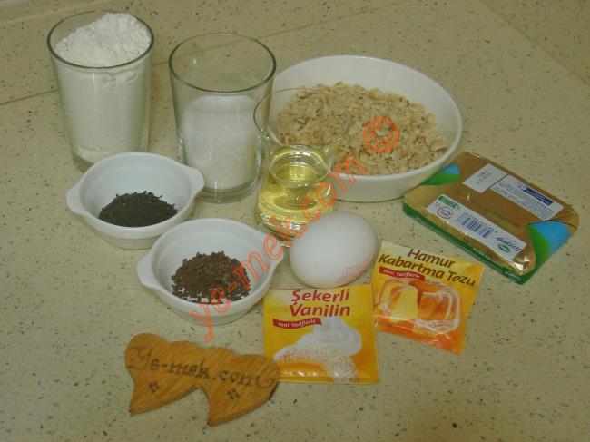 Çaylı Kurabiye İçin Gerekli Malzemeler :  <ul> <li>125 gr tereyağı (oda sıcaklığında)</li>         <li>1/2 çay bardağı sıvı yağ</li> <li>1 adet yumurta sarısı (akı bulamak için)</li> <li>1/2 su bardağı toz şeker</li> <li>1 yemek kaşığı kuru çay</li> <li>1 tatlı kaşığı nescafe</li>         <li>1 paket kabartma tozu</li> <li>1 paket vanilya</li> <li>2 su bardağı un</li>         <li><strong>Üzeri İçin:</strong></li>         <li>Orta dövülmüş fındık ya da ceviz</li>  </ul>