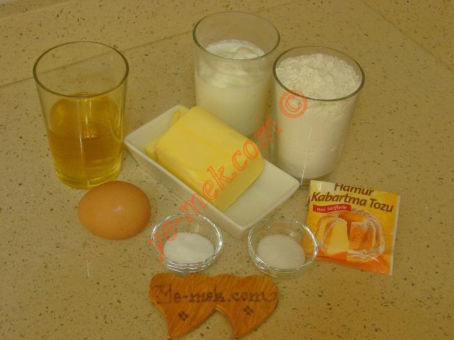 Gevrek Poğaça İçin Gerekli Malzemeler :  <ul> <li>125 gr tereyağı (Oda sıcaklığında)</li> <li>1/2 su bardağı zeytinyağı</li> <li>1 yumurta akı (Sarısı üzerine)</li>         <li>1 su bardağından iki parmak eksik yoğurt</li> <li>1 tatlı kaşığı tuz</li>         <li>1 tatlı kaşığı toz şeker</li> <li>1 paket kabartma tozu</li>         <li>3 su bardağı un</li> <li><strong>Üzeri İçin:</strong></li> <li>Yumurta sarısı</li>         <li>Susam</li> </ul>