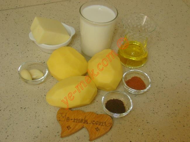 Sütlü Patates İçin Gerekli Malzemeler :  <ul> <li>3 adet orta boy patates</li>         <li>1 su bardağı süt</li>         <li>2 diş rendelenmiş sarımsak</li>         <li>1 tatlı kaşığı silme sumak</li>         <li>1 tatlı kaşığı kırmızı toz biber</li>         <li>2 yemek kaşığı zeytinyağı</li>         <li>Tuz, karabiber</li>         <li><strong>Üzeri İçin:</strong></li>         <li>Rendelenmiş kaşar peynir</li>  </ul>