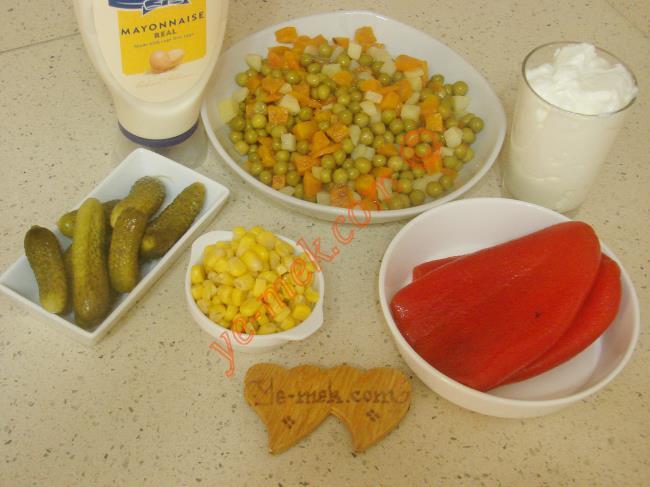 Yoğurtlu Garnitür Salatası İçin Gerekli Malzemeler :  <ul> <li>1 kavanoz hazır garnitür</li>         <li>5 yemek kaşığı konserve mısır</li>         <li>3 adet közlenmiş kırmızı biber</li>         <li>7 adet kornişon turşu</li>         <li>3 yemek kaşığı mayonez</li>         <li>1 su bardağı katı yoğurt</li>         <li>Tuz</li> </ul>