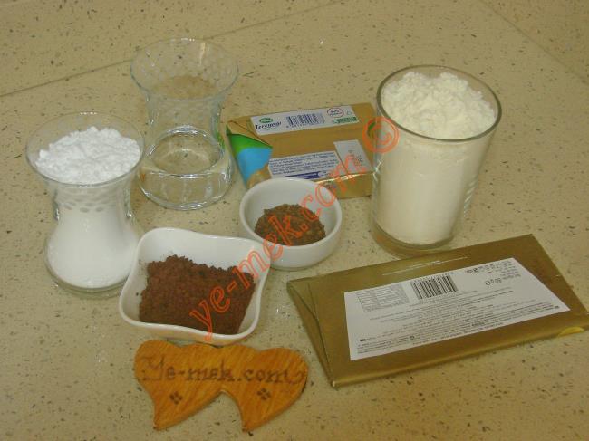 Kahveli Kurabiye İçin Gerekli Malzemeler :  <ul> <li>100 gr tereyağı (oda sıcaklığında)</li>         <li>1 çay bardağı pudra şekeri</li> <li>1 yemek kaşığı dolusu kakao</li> <li>1 tatlı kaşığı nescafe</li>         <li>1 tatlı kaşığı su</li> <li>1,5 su bardağı un</li>         <li><strong>Üzeri İçin:</strong></li>         <li>80 gr bitter ya da sütlü çikolata</li> </ul>