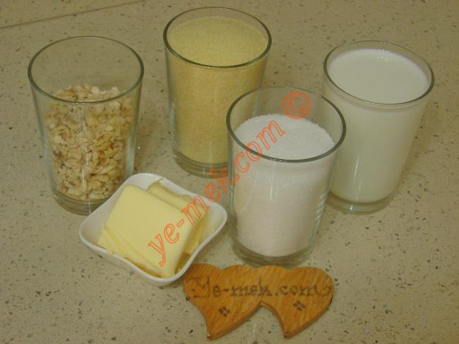 Sütlü İrmik Helvası İçin Gerekli Malzemeler :  <ul> <li>1 su bardağı irmik</li> <li>50 gr tereyağı</li>         <li>1/2 su bardağı dövülmüş fındık</li>         <li><strong>Şerbeti İçin:</strong></li> <li>1,5 su bardağı süt</li> <li>1 su bardağından 1 parmak az toz şeker</li> </ul>