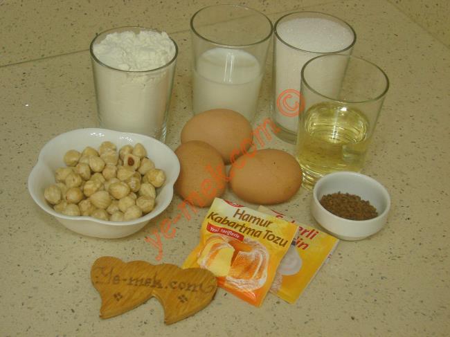 Kahveli Kek İçin Gerekli Malzemeler :  <ul> <li>3 adet yumurta (Oda ısısında)</li>         <li>1 su bardağı dolusu toz şeker</li>         <li>1/2 su bardağı süt</li> <li>1/2 su bardağı sıvı yağı</li>         <li>1 yemek kaşığı nescafe</li>         <li>1 tatlı kaşığı toz şeker</li>         <li>1 çay bardağı ılık su</li>         <li>1 su bardağı fındık kırığı</li> <li>1 paket kabartma tozu</li> <li>1 paket vanilya</li>         <li>2,5 su bardağı un</li> </ul>