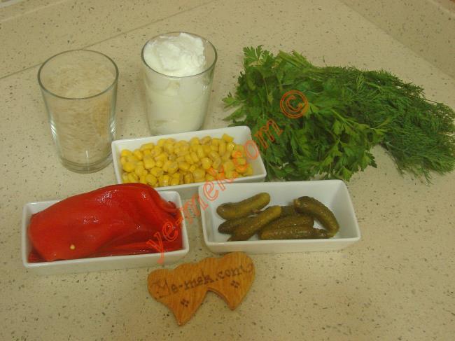 Yoğurtlu Pirinç Salatası İçin Gerekli Malzemeler :  <ul> <li>1 su bardağı pirinç</li>         <li>2,5 su bardağı sıcak su</li>         <li>2,5 su bardağı yoğurt</li>         <li>1/2 su bardağı konserve mısır</li>         <li>2 adet közlenmiş kırmızı biber</li>         <li>7 adet kornişon turşu</li>         <li>2 tutam maydanoz</li>         <li>2 tutam dereotu</li>         <li>Tuz</li> </ul>