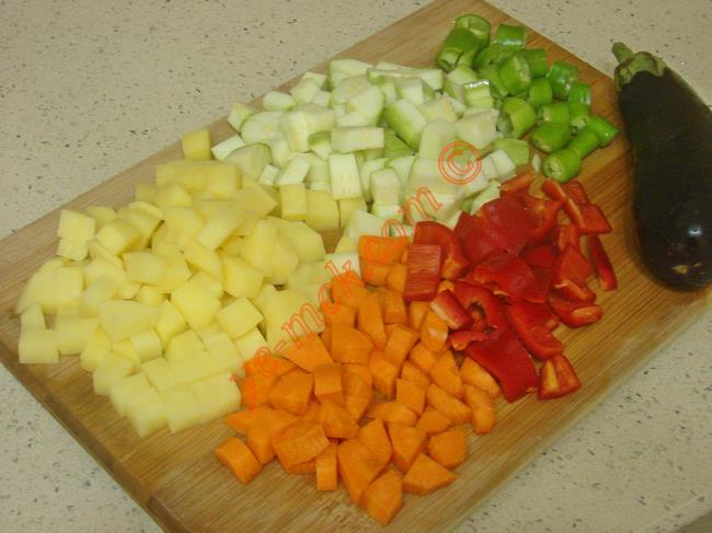 Sebzeli makarna mantısı yapımında öncelikle 1 er adet büyük boy kabak, patlıcan, patates ve havucun kabuğunu soyun. Yıkayıp, küçük küpler halinde kesin. 1 adet büyük boy kırmızı kapya biber ve 1 adet yeşil biberin de çekirdeklerini temizleyip, orta büyüklükte küpler halinde kesin.