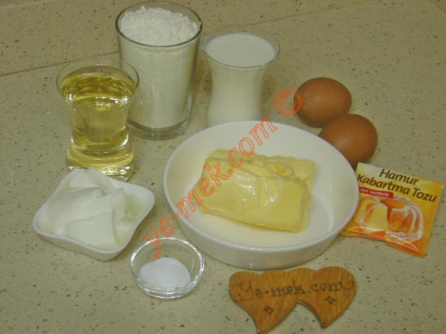 Ağızda Dağılan Mayasız Poğaça İçin Gerekli Malzemeler :  <ul> <li>150 gr tereyağı (Oda sıcaklığında)</li>         <li>2 adet yumurta (Birinin sarısı üzerine)</li> <li>1 çay bardağı sıvı yağ</li>         <li>1 çay bardağı süt</li>         <li>2 yemek kaşığı yoğurt</li>         <li>1 tatlı kaşığı tuz</li> <li>1 paket kabartma tozu</li>         <li>5 su bardağı un</li>         <li><strong>İç Malzemesi İçin:</strong></li>         <li>Beyaz peynir</li>         <li>Maydanoz</li> <li><strong>Üzeri İçin:</strong></li> <li>Yumurta sarısı</li>         <li>Çörek otu</li> </ul>
