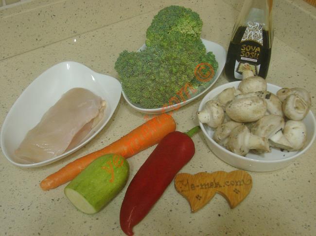 Tavada Sebzeli Tavuk İçin Gerekli Malzemeler :  <ul> <li>350 gr tavuk göğsü</li>         <li>150 gr brokoli</li> <li>200 gr kültür mantarı</li> <li>1 adet orta boy havuç</li>         <li>1/2 orta boy kabak</li>         <li>1 adet kırmızı kapya biber</li>         <li>4 yemek kaşığı zeytinyağı</li>         <li>3 yemek kaşığı soya sosu</li>         <li>Az miktar tuz</li>  </ul>