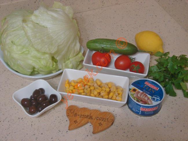 Ton Balıklı Salata İçin Gerekli Malzemeler :  <ul> <li>5 yaprak marul</li>         <li>1 tutam maydanoz</li>         <li>3 adet çeri domates</li>         <li>1 kutu orta boy ton balığı</li>         <li>1 adet küçük boy salatalık</li>         <li>3 yemek kaşığı konserve mısır</li>         <li>5 adet siyah zeytin</li>         <li>1/2 limon suyu</li>         <li>2 yemek kaşığı zeytinyağı</li>         <li>Tuz</li> </ul>