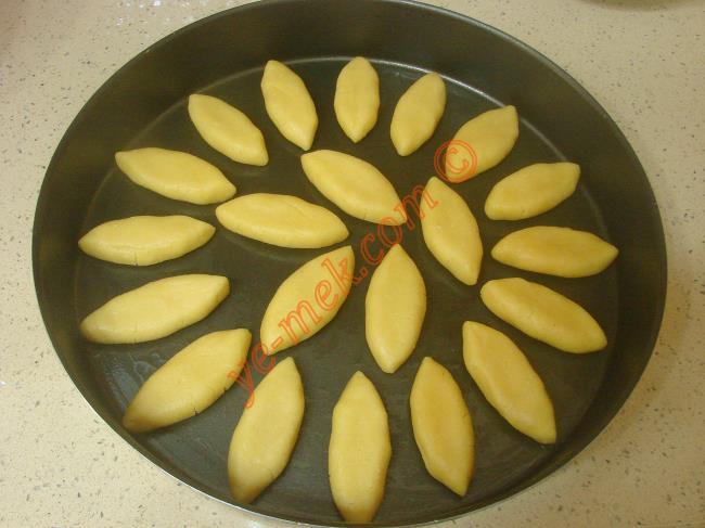 Yoğurduğunuz hamurdan ceviz büyüklüğünde parçalar kopartın. Avuç içinde yuvarlayıp, oval şeklini verin.