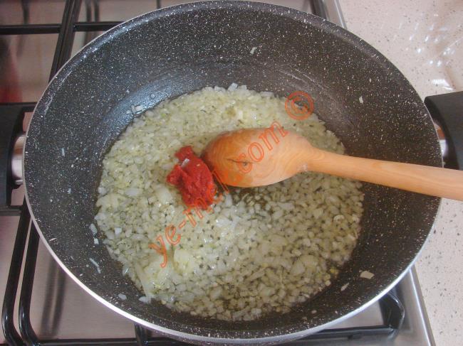 1 adet küçük boy soğan ve 2 diş sarımsağı ince ince doğrayın.  Orta boy geniş bir tencere içine doğranmış soğan ve sarımsakları koyun.