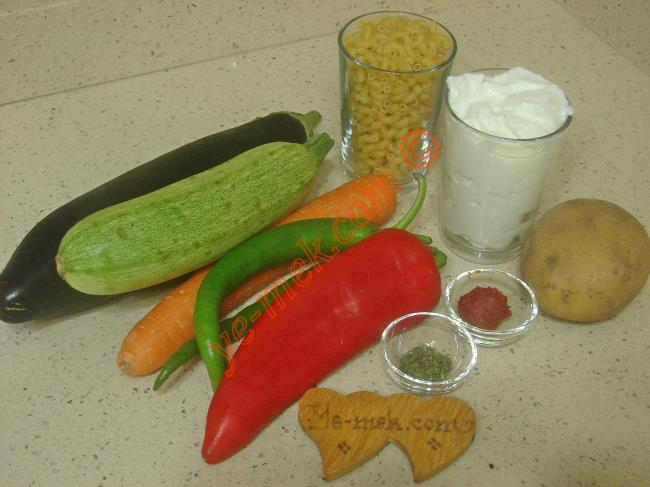 Sebzeli Makarna Salatası İçin Gerekli Malzemeler :  <ul> <li>1 adet büyük boy patlıcan</li> <li>1 adet büyük boy kabak</li> <li>1 adet büyük boy patates</li>         <li>1 adet büyük boy havuç</li>         <li>1 adet büyük boy kırmızı kapya biber</li>         <li>1 adet büyük boy yeşil biber</li>         <li>2 su bardağı küçük makarna</li>         <li>Kızartmak için sıvı yağ</li>         <li><strong>Yoğurt Sosu İçin:</strong></li>         <li>1,5 su bardağı yoğurt</li>         <li>1 diş rendelenmiş sarımsak</li>         <li>Az miktar tuz</li>         <li><strong>Üzeri İçin:</strong></li>         <li>Sıvı yağ</li>         <li>Kuru nane, kırmızı toz biber</li> </ul>Sebzeli makarna salatası yapımında; öncelikle orta boy derin bir tencere içine yeteri miktarda su koyup, kaynamaya bırakın. Kaynayan suyun içine tuz ve 2 su bardağı küçük makarnayı ekleyin. Makarnayı yumuşayana kadar haşlayın. Ardından suyunu süzüp, 1-2 kez soğuk sudan geçirin.