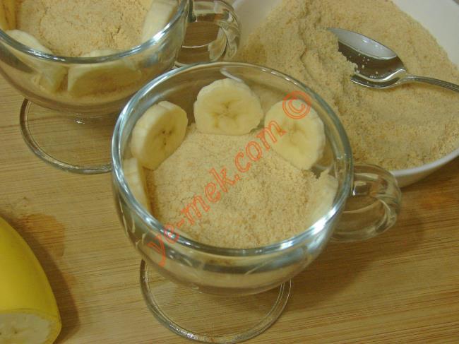 Pudingin üzerine rondodan geçirdiğiniz bisküviden biraz koyun. Kenar kısımlarına muz dilimleri yerleştirin.