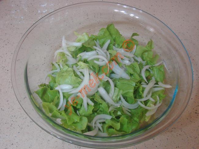 Marul salatası için; 6 adet büyük yaprak kıvırcık marulu iyice yıkayıp, kurulayın. Çukur bir kap içine marul yapraklarını eliniz ile biraz iri olacak şekilde parçalayarak, koyun. Ardından 1 adet küçük boy soğanın kabuğunu soyup, söğüş olarak doğrayın. Yumuşaması için biraz tuz ile ovalayın. Marulların üzerine ekleyin.