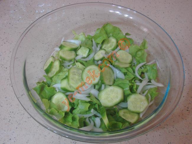 Daha sonra 2 adet küçük boy salatalığı halkalar halinde kesip, salata kabına koyun.