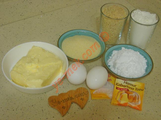 Fındıkpare Tatlısı İçin Gerekli Malzemeler :  <ul> <li>250 gr tereyağ ya da margarin (Oda Isısında)</li> <li>2 adet yumurta (Birinin sarısı üzerine)</li> <li>7 yemek kaşığı pudra şekeri</li> <li>7 yemek kaşığı irmik</li> <li>1,5 su bardağı çekilmiş fındık</li> <li>1 paket kabartma tozu</li>         <li>1 paket vanilya</li> <li>3,5 su bardağı un</li>  <li><strong>Şerbeti İçin:</strong></li> <li>3 su bardağı su</li> <li>3 su bardağı toz şeker</li> <li>3 damla limon suyu</li>         <li><strong>Üzeri İçin:</strong></li> <li>Yeşil toz fıstık</li> </ul>