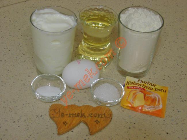 Yoğurtlu Poğaça İçin Gerekli Malzemeler :  <ul> <li>1 su bardağı yoğurt</li> <li>1 çay bardağı sıvı yağ</li> <li>1 adet yumurta akı (Sarısı üzerine)</li>         <li>1 tatlı kaşığı tuz</li>         <li>1 yemek kaşığı toz şeker</li> <li>1 paket kabartma tozu</li>         <li>3 su bardağı un</li>         <li><strong>İç Malzemesi İçin:</strong></li>         <li>Beyaz peynir</li>         <li>1 tutam maydanoz</li> <li><strong>Üzeri İçin:</strong></li> <li>Yumurta sarısı</li>         <li>Susam</li> </ul>
