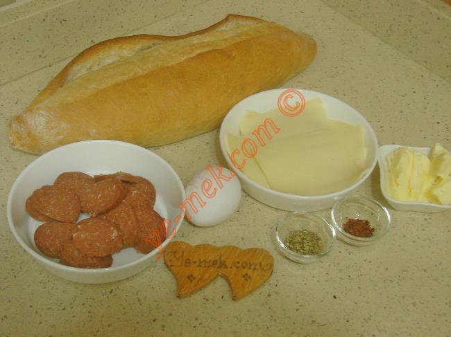 Yumurtalı Tost İçin Gerekli Malzemeler :  <ul> <li>1 adet somun ekmek</li>         <li>1 adet yumurta</li> <li>8 dilim sucuk</li> <li>5 dilim kaşar peynir</li>         <li>1 yemek kaşığı tereyağı</li>         <li>Kekik</li>         <li>Kırmızı pul biber</li> </ul>