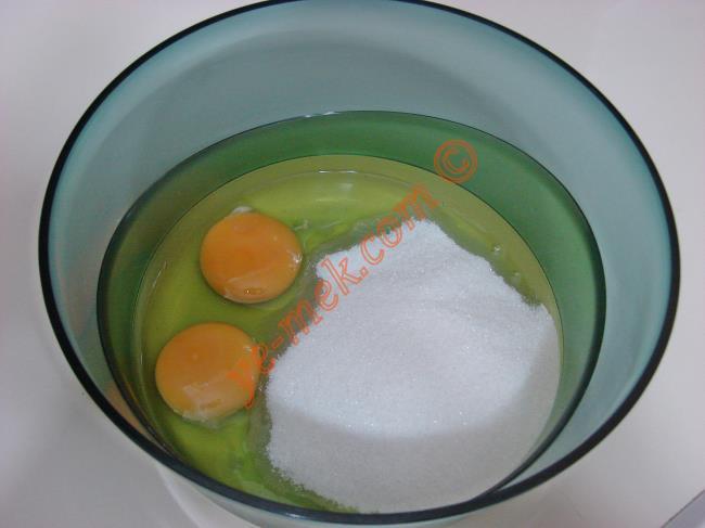 Havuçlu tarçınlı kek yapımında; öncelikle 2 adet orta boy havucun kabuğunu soyup, rendenin kalın tarafı ile rendeleyin. Derin bir kaba 2 adet yumurta kırın. Üzerine 1 su bardağı toz şeker ekleyin.