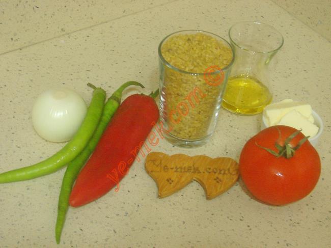 Biberli Bulgur Pilavı İçin Gerekli Malzemeler :  <ul>         <li>1 su bardağı pilavlık bulgur</li> <li>1 adet küçük boy soğan</li>         <li>2 adet sivri biber</li>         <li>1 adet orta boy domates</li>         <li>1 adet orta boy kırmızı kapya biber</li>         <li>1 yemek kaşığı tereyağı</li>         <li>2 yemek kaşığı zeytinyağı</li>         <li>2 su bardağı sıcak su</li> <li>Tuz</li> </ul>