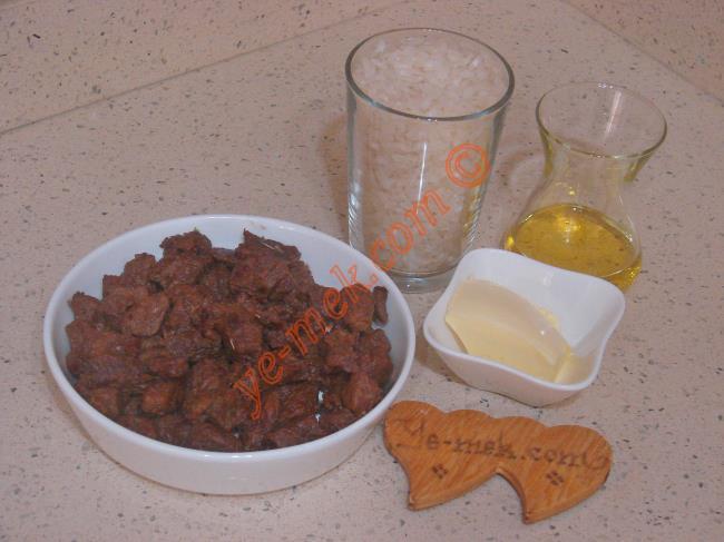 Etli Pilav İçin Gerekli Malzemeler :  <ul> <li>250 gr kuşbaşı doğranmış et</li>         <li>1 su bardağı pilavlık pirinç</li>         <li>1 yemek kaşığı tereyağı</li>         <li>1 yemek kaşığı zeytinyağı</li>         <li>1,5 su bardağı sıcak su</li> <li>Tuz</li> </ul>