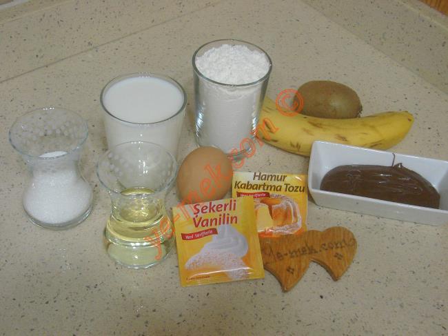 Waffle İçin Gerekli Malzemeler :  <ul>         <li><strong>Hamuru İçin:</strong></li>    <li>1 adet yumurta</li>  <li>1 su bardağı süt</li> <li>1/2 çay bardağı toz şeker</li>         <li>1/2 çay bardağı sıvı yağ</li>         <li>1 paket vanilya</li>         <li>1 çay kaşığı kabartma tozu</li> <li>1,5 su bardağı un</li>         <li><strong>Süslemek İçin:</strong></li>         <li>Çilek, muz, kivi</li>         <li>Krem çikolata</li>         <li>Dövülmüş fındık ve fıstık</li> </ul>