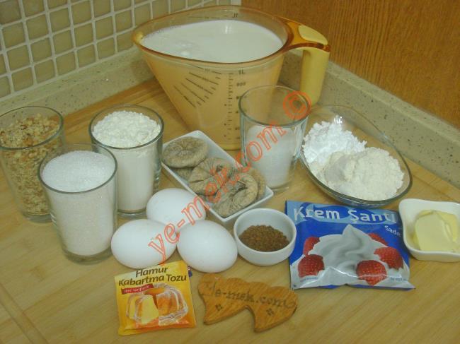 Muhallebili İncir Tatlısı İçin Gerekli Malzemeler :  <ul>         <li><strong>Kek İçin:</strong></li> <li>3 adet yumurta (Oda ısısında)</li>         <li>1 su bardağı toz şeker</li>         <li>1 su bardağı un</li> <li>1 paket kabartma tozu</li> <li>1 su bardağı dövülmüş ceviz</li>         <li>6 adet kuru incir</li>         <li><strong>Kekin Şerbeti İçin:</strong></li>         <li>1 yemek kaşığı nescafe</li> <li>1/2 su bardağı toz şeker</li>         <li>1,5 su bardağı ılık su</li>         <li><strong>Muhallebisi İçin:</strong></li>         <li>1 litre süt</li>         <li>2 tepeleme yemek kaşığı un</li>         <li>2 tepeleme yemek kaşığı nişasta</li>         <li>5 yemek kaşığı toz şeker</li>         <li>1 yemek kaşığı tereyağı</li>         <li>1 paket toz krem şanti</li> </ul>