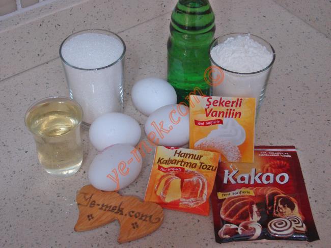 Sodalı Kek İçin Gerekli Malzemeler :  <ul> <li>4 adet yumurta (Oda sıcaklığında)</li>         <li>1,5 su bardağı toz şeker</li>         <li>1 şişe maden suyu (200 ml)</li> <li>1 çay bardağı sıvı yağ</li> <li>1 paket kabartma tozu</li> <li>1 paket vanilya</li>         <li>2,5 su bardağı un</li>         <li><strong>Daha sonra eklemek için:</strong></li>         <li>2 yemek kaşığı kakao</li>         <li>2 yemek kaşığı un</li>       </ul>