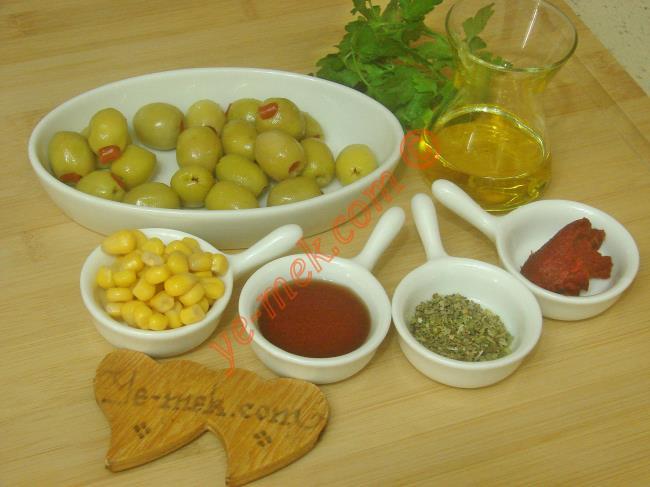 Yeşil Zeytin Salatası İçin Gerekli Malzemeler :  <ul> <li>20 adet yeşil zeytin</li> <li>1 tatlı kaşığı biber salçası</li>         <li>1 yemek kaşığı nar ekşisi</li>         <li>4 yemek kaşığı zeytinyağı</li>         <li>1 yemek kaşığı konserve mısır</li>         <li>1 tatlı kaşığı kekik</li> <li>1 tutam maydanoz</li> <li>Tuz</li> </ul>