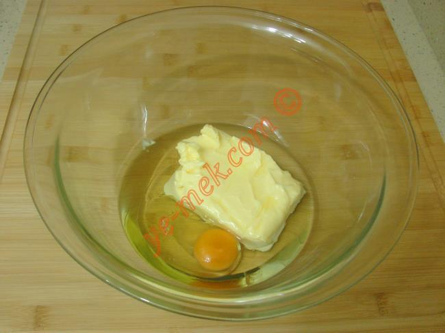 Dondurma kurabiye yapımı için; derin bir kaba oda sıcaklığındaki 200 gr tereyağı ya da margarini koyun. Üzerine 1 adet yumurta kırıp, 1 çay bardağı sıvı yağ ekleyin. Tel çırpıcı yardımı ile iyice karıştırın.