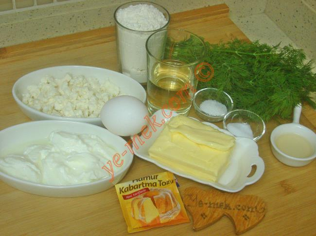 Mayasız Peynirli Dereotlu Poğaça İçin Gerekli Malzemeler :  <ul> <li>125 gr tereyağı (Oda sıcaklığında)</li> <li>1/2 su bardağı sıvı yağı</li> <li>5 yemek kaşığı yoğurt</li>         <li>1 yemek kaşığı elma sirkesi</li>         <li>1 adet yumurta akı</li> <li>1 tatlı kaşığı tuz</li> <li>1 tatlı kaşığı toz şeker</li> <li>1 paket kabartma tozu</li> <li>1/2 demetten biraz fazla dereotu</li> <li>3,5 su bardağı un</li>         <li><strong>İçi İçin:</strong></li>         <li>Beyaz peynir</li>         <li>Kaşar peynir</li> <li><strong>Üzeri İçin:</strong></li> <li>Yumurta sarısı</li> <li>Susam</li> </ul>