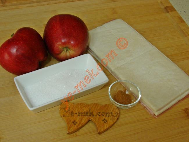 Elmalı Milföy Kurabiye İçin Gerekli Malzemeler :  <ul> <li>8 adet kare milföy hamuru</li>         <li>2 adet orta boy elma</li>         <li>3 yemek kaşığı toz şeker</li>         <li>1 çay kaşığı tarçın</li>         <li><strong>Üzeri İçin:</strong>         <li>Pudra şekeri</li>  </ul>