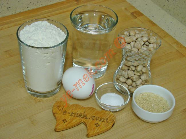 Nohut Mayalı Köy Ekmeği İçin Gerekli Malzemeler :  <ul>         <li><strong>Nohut Mayası İçin:</strong></li> <li>1 çay bardağı nohut</li> <li>2 su bardağı kaynar su</li>         <li>1,5 su bardağı un</li>         <li><strong>Hamuru İçin:</strong></li>         <li>2,5 su bardağı un</li>         <li>1 tatlı kaşığı tuz</li>         <li><strong>Üzeri İçin:</strong></li>         <li>Yumurta sarısı</li>         <li>Susam</li> </ul>