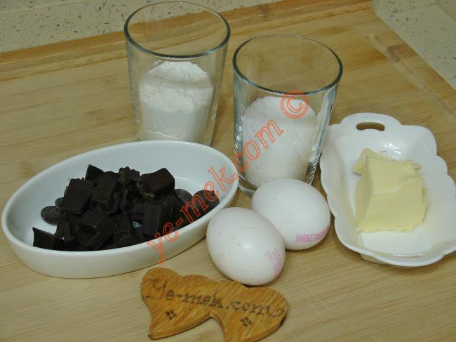 Sufle İçin Gerekli Malzemeler :  <ul> <li>2 adet yumurta</li> <li>1/2 su bardağı un</li> <li>1/2 su bardağı toz şeker</li> <li>80 gr bitter çikolata</li> <li>50 gr tereyağı</li> <li><strong>Üzeri İçin:</strong></li>         <li>Pudra şekeri</li>  </ul>