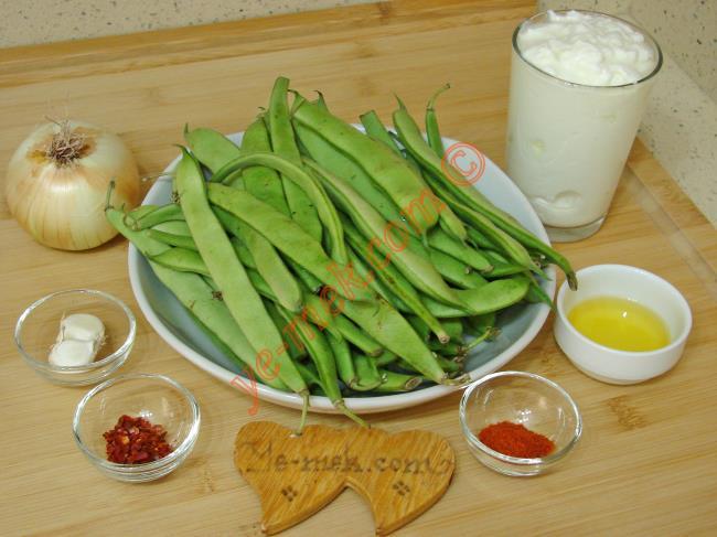 Taze Fasulye Borani İçin Gerekli Malzemeler :  <ul> <li>500 gr taze fasulye</li>         <li>1 adet orta boy soğan</li>         <li>4 yemek kaşığı zeytinyağı</li> <li>Tuz</li>         <li><strong>Üzeri İçin:</strong></li>         <li>1,5 su bardağı katı yoğurt</li>         <li>2 diş sarımsak</li>         <li>2 yemek kaşığı zeytinyağı</li>         <li>Kırmızı toz biber</li>         <li>Kırmızı pul biber</li> </ul>