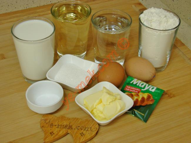 Yumuşak Sade Poğaça İçin Gerekli Malzemeler :  <ul> <li>1 su bardağı ılık su</li>         <li>1 su bardağı süt</li>         <li>1 su bardağı sıvı yağ</li>         <li>2 adet yumurta akı (sarılar üzerine)</li> <li>1 paket instant kuru maya</li> <li>2 yemek kaşığı toz şeker</li> <li>1,5 tatlı kaşığı tuz</li>         <li>6 su bardağı un</li>         <li>1,5 yemek kaşığı yumuşak tereyağı</li> <li><strong>Üzeri İçin:</strong></li> <li>Yumurta sarısı</li>         <li>Susam</li> </ul>