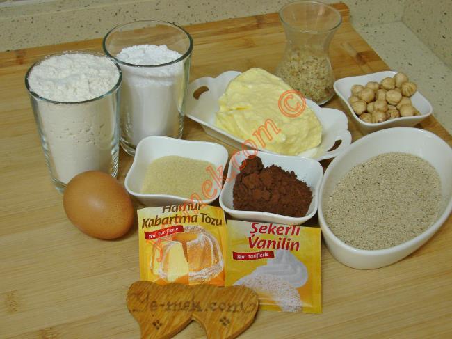 Melisa Tatlısı İçin Gerekli Malzemeler :  <ul> <li>125 gr tereyağı (Oda sıcaklığında)</li>         <li>1 adet yumurta</li>         <li>1 su bardağından 1 parmak az pudra şekeri</li>         <li>2 yemek kaşığı kakao</li> <li>2,5 yemek kaşığı irmik</li>         <li>1/2 çay bardağı öğütülmüş ceviz</li>         <li>1 paket vanilya</li>         <li>1 paket kabartma tozu</li>         <li>2 su bardağı un</li> <li><strong>Şerbeti İçin:</strong></li> <li>3 su bardağı toz şeker</li>         <li>3 su bardağı su</li>          <li>3 damla limon suyu</li>         <li><strong>Üzeri İçin:</strong></li>         <li>Beyaz haşhaş</li>         <li>Fındık</li> </ul>