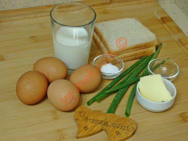Sütlü Yumurta İçin Gerekli Malzemeler :  <ul> <li>4 adet yumurta</li> <li>1/2 su bardağı süt</li>         <li>1 yemek kaşığı tereyağı</li>         <li>Tuz</li>         <li>Karabiber</li>         <li>2 dilim tost ekmeği</li>         <li><strong>Üzeri İçin:</strong></li>         <li>Taze soğan yaprağı</li> </ul>