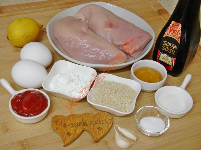 Ballı Susamlı Tavuk İçin Gerekli Malzemeler :  <ul> <li>500 gr tavuk göğüs eti</li> <li>2 adet yumurta</li>         <li>3 yemek kaşığı mısır nişastası</li> <li>Kızartmak için sıvı yağ</li>         <li><strong>Sosu İçin:</strong> <li>3 yemek kaşığı susam</li>         <li>2 yemek kaşığı ketçap</li> <li>2 yemek kaşığı soya sosu</li> <li>2 yemek kaşığı limon suyu</li>         <li>1 tatlı kaşığı toz şeker</li>         <li>2 yemek kaşığı bal</li>         <li>2 diş sarımsak</li>         <li>Tuz</li>         <li>Karabiber</li> </ul>